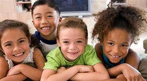 four smiling multi cultural children lined up